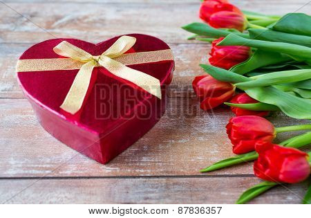 flowers, valentines day and holidays concept - close up of red tulips and heart shaped chocolate box on wooden table