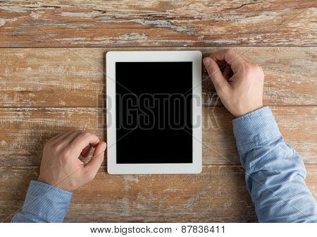 business, education, people and technology concept - close up of male hands with tablet pc computer on table