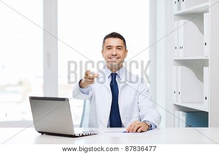 profession, gesture, people, technology and medicine concept - smiling male doctor in white coat pointing finger at you in medical office
