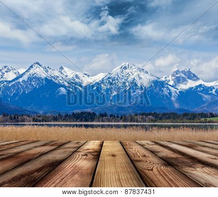 Wooden planks floor with Bavarian Alps countryside lake landscape in background. Bavaria, Germany