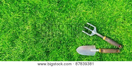 Gardening tools on green grass. Spring and summer background.