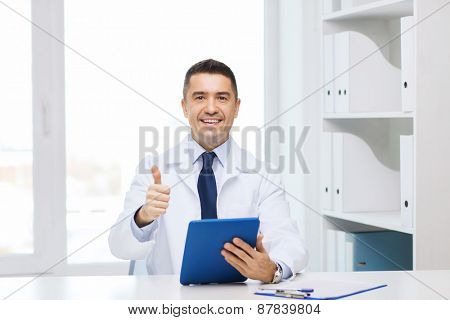 healthcare, profession, people and medicine concept - smiling male doctor in white coat with tablet pc computer showing thumbs up in medical office