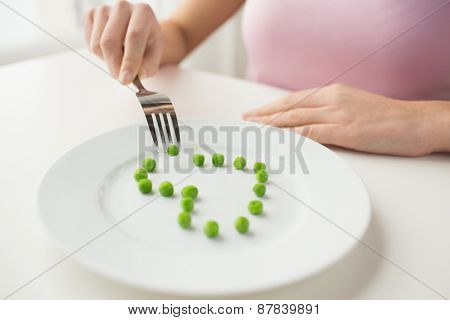 healthy eating, dieting, vegetarian food and people concept - close up of woman with fork eating peas in shape of heart