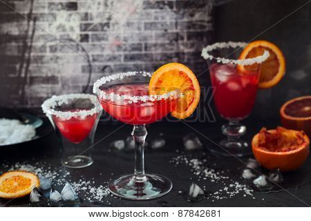 Blood Orange Margarita in glass with salted rim.