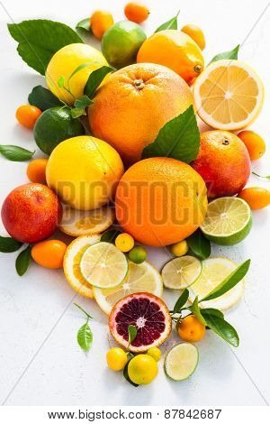 Assorted fresh citrus fruits with leaves.