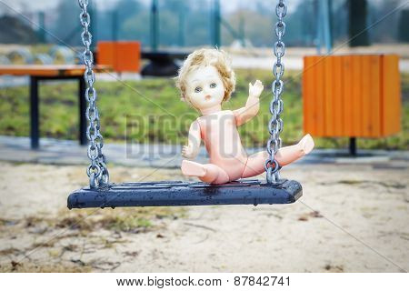 Old abandoned doll on a swing