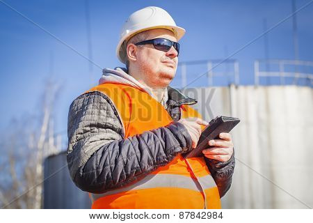Engineer with tablet PC with oil tank in the background