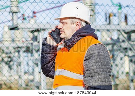 Electrical engineer talking on cell phone at power station
