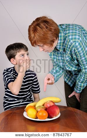 Woman showing fruit to a young boy