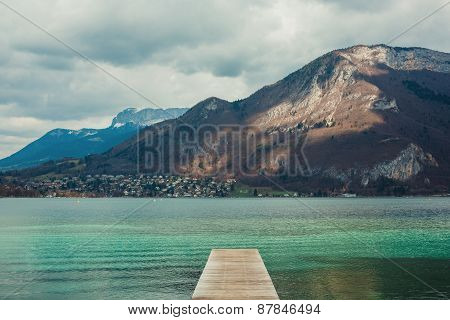 Pier On The Mountain Lake With City On Background