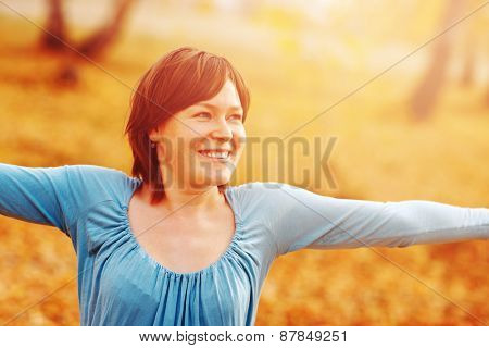 Young woman arms raised enjoying the fresh air in autumn forest.