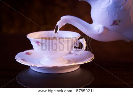 Old-style Pouring Tea To Cup On Black Background