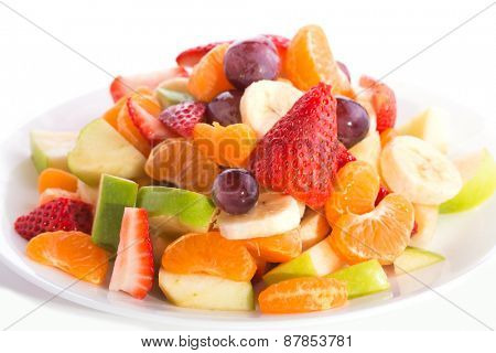 Colorful fruit salad heaped on white plate