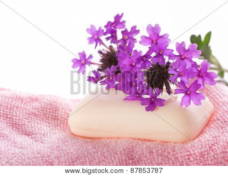 Soap on pink wash cloth, with deep purple wildflowers on top, on white background