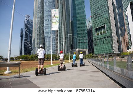 SINGAPORE - CIRCA FEBRUARY, 2015: Young people riding on an electric scooter along the waterfront Marina Bay in Singapore. Quay Marina Bay a popular place for walks among the tourists and locals.