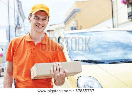 Smiling postal delivery courier man outdoors  in front of cargo van delivering package
