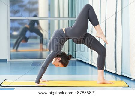 fitness woman doing gymnastic physical training exercise in gym