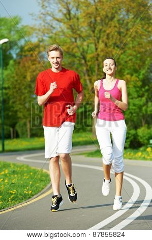 Young fitness man and woman doing jogging run sport outdoors