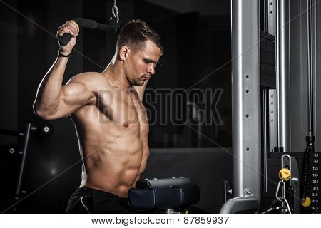 Brutal athletic man pumping up muscles in a gym