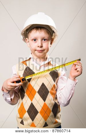 The Boy In The Construction Helmet And A Tape Measure In Hand