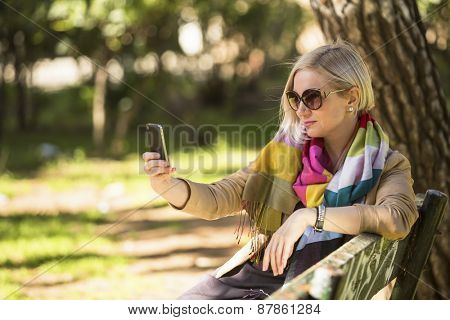 Blonde woman doing a self-portrait with smartphone sitting on bench in the Park.
