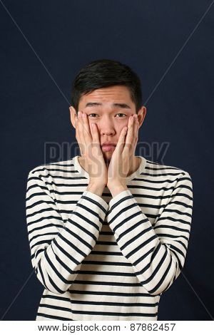 Disappointed young Asian man covering his face by palms and looking at camera