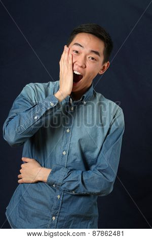 Astonished young Asian man looking at camera