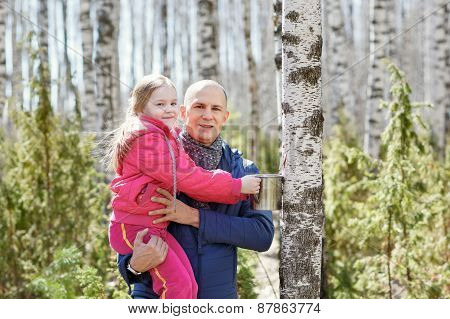 family in wood collecting birch sap mug