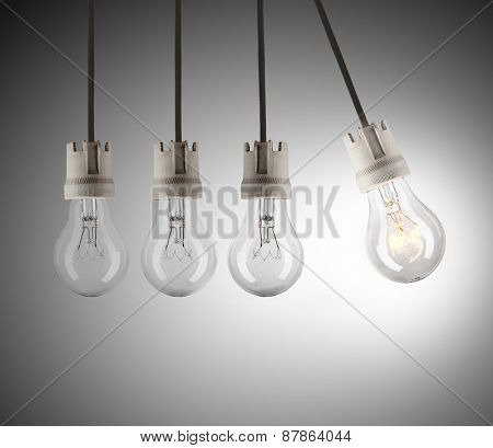 Light bulbs in row with single one in motion and shinning