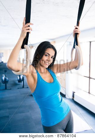 Young smiling woman working out on gimnastic rings at gym. Lookint at camera