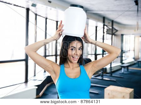 Laughing young fit woman with plastic container on head and looking at camera
