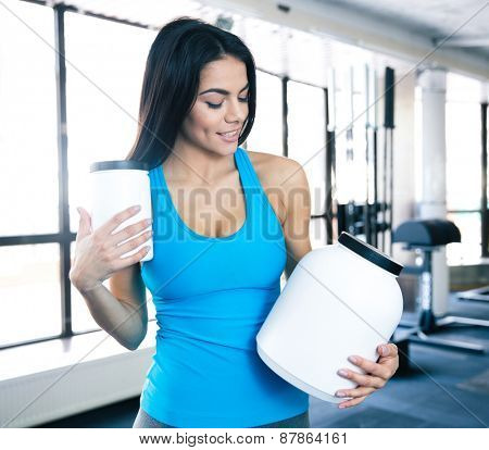 Happy young woman holding plastic container with sports nutrtion at gym and looking on container