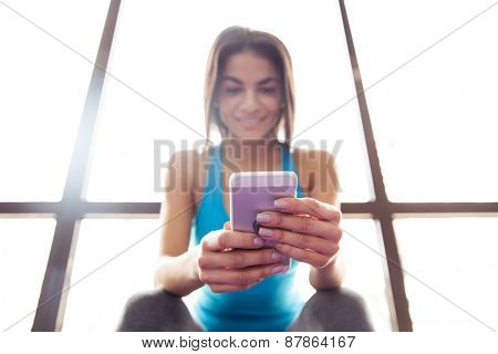 Happy beautiful woman using smartphone at gym. Focus on smartphone