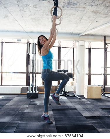 Smiling woman working out on gimnastic rings at gym and looking away