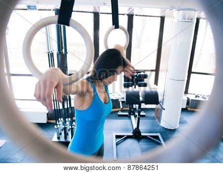Tired woman working out on gimnastick rings at gym