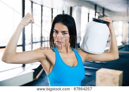 Fit woman showing her muscles and holding sports nutrition at gym. Looking at camera