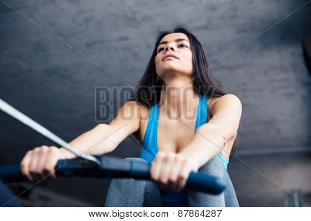 Beautiful woman working out on training simulator in fitness gym