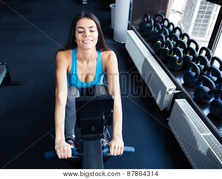 Happy young cute woman working out on a simulator at gym