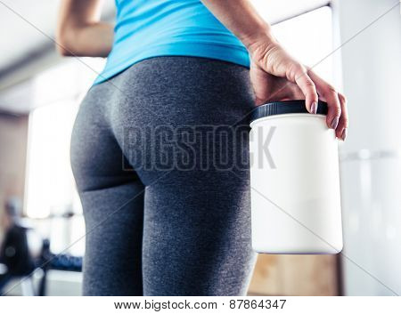 Closeup image of female body with sports nutrition at gym