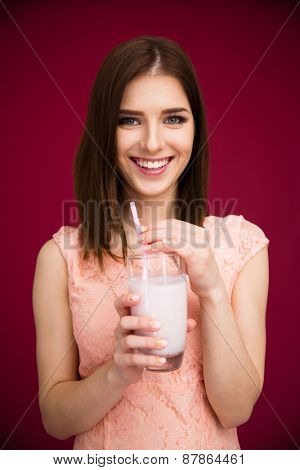 Smiling woman holding glass with yogurt over pink background. Looking at camera.
