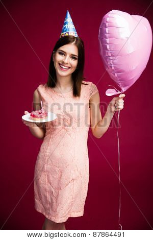 Happy beautiful woman holding heart shaped balloon and donut with candle. Standing over pink background. Looking at camera. Wearing in dress