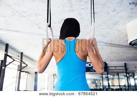 Rear view portrait of woman working out on gimnastic rings at gym