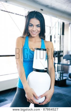 Happy young woman holding plastic container with sports nutrtion at gym and looking at camera