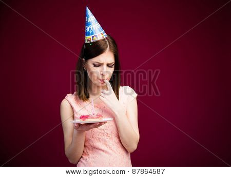 Young cute woman holding donut with candle over pink background