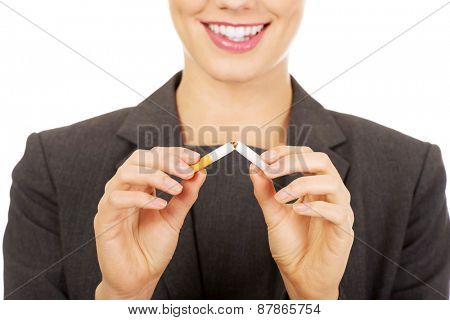 Businesswoman holding out and breaking a cigarette.