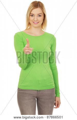 Young casual woman pointing at camera.