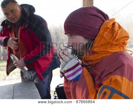 Man And Woman Sitting In A Wooden Gazebo In The Woods And Drink From A Thermos.