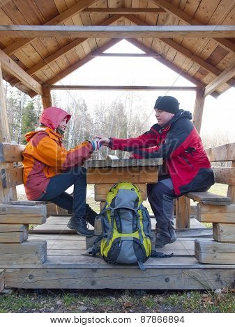 Tourists Sitting In A Wooden Gazebo At The Table And Drink From A Thermos.