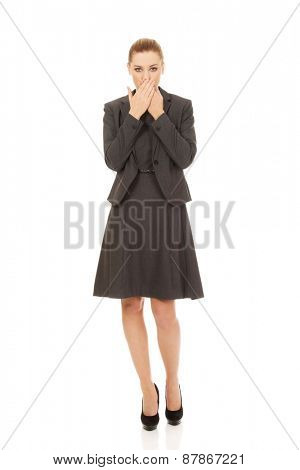 Young businesswoman covering mouth with hands.