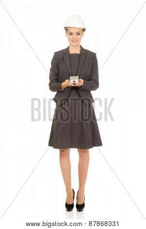 Businesswoman in hard hat holding small model house.